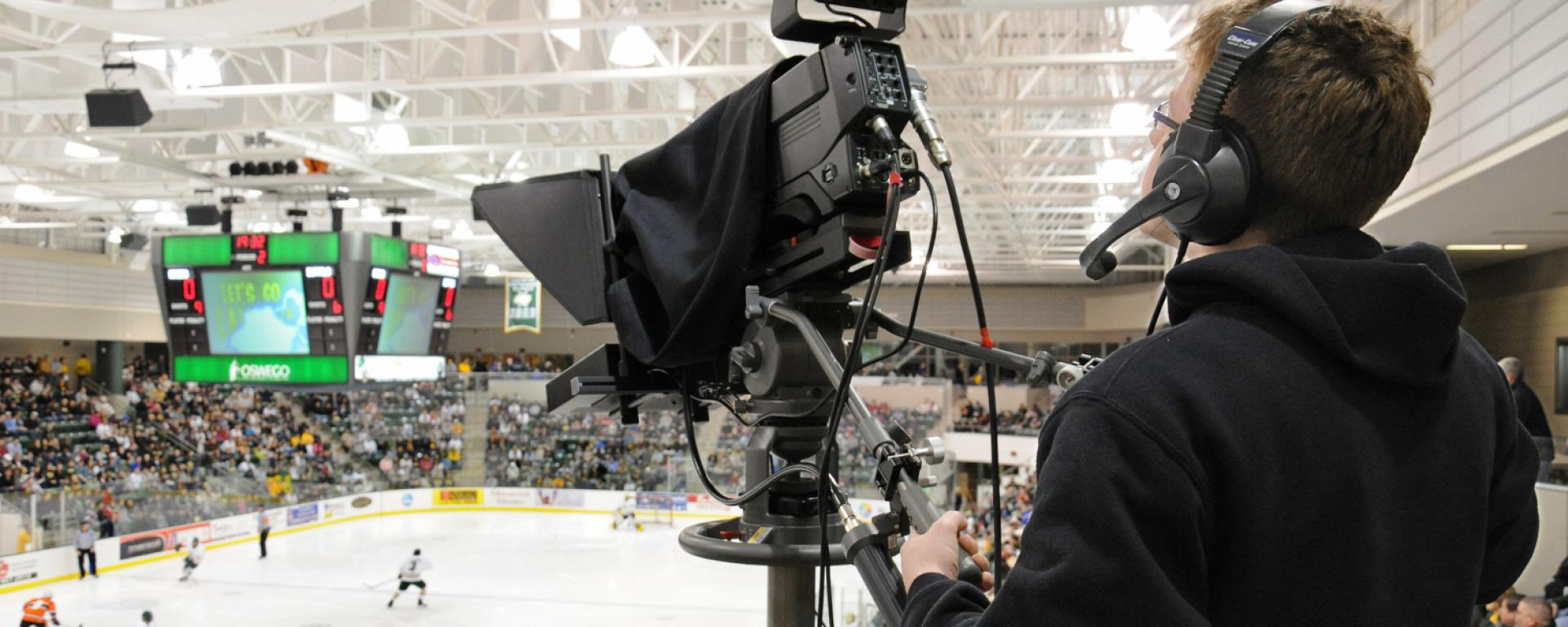 Student filming live hockey broadcast
