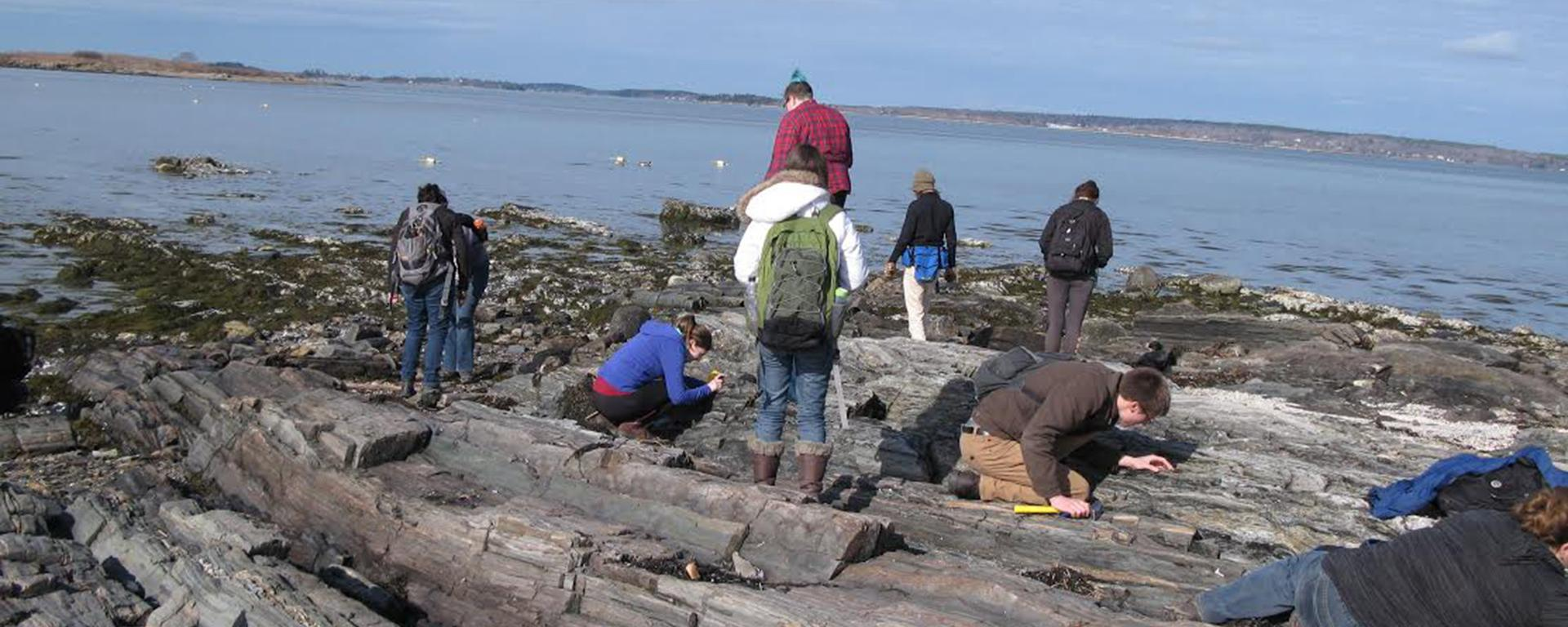 Students studying rock formations near water