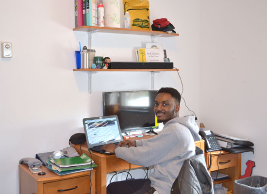 male student working at his desk in his village townhouse bedroom.