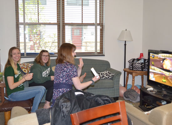 residents in the village townhouse have fun playing a video game on their widescreen tv in their furnished living room