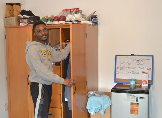 student taking a shirt out of this wardrobe in his village townhouse bedroom