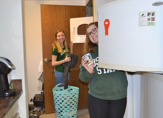 student takes and item out of her full size fridge while her roommate does her laundry in the kitchen of their village townhouse