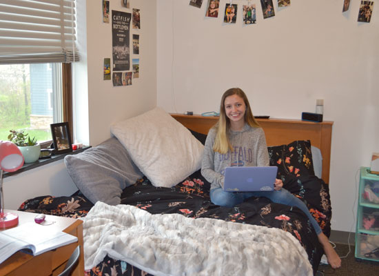 resident of the village townhouse sits on her full size bed in her fully furnished bedroom