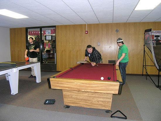 Students enjoy playing pool, ping-pong and basketball in the spacious Cayuga Hall main lounge.