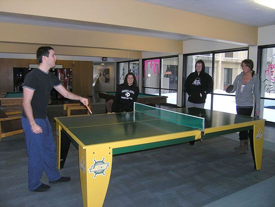 A group of students have fun playing ping-pong in Oneida hall's spacious main floor lounge.