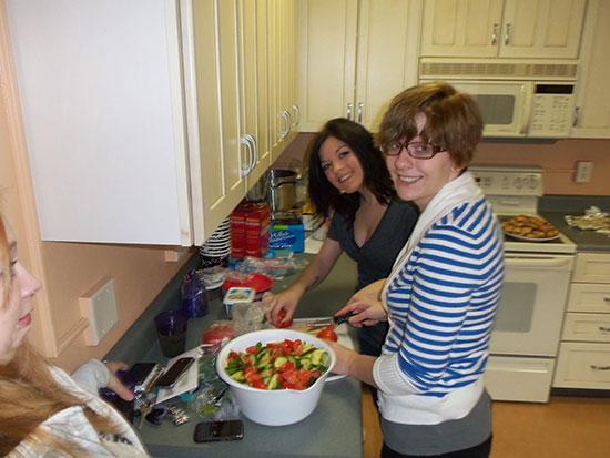 Female students prepare a salad in the Mackin Complex kitchen.
