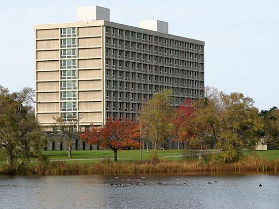 Ducks swim in a row across Glimmerglass Lagoon behind Seneca Hall on a clear autumn day.