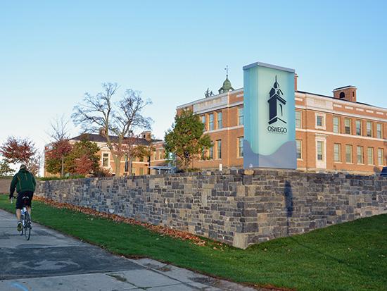 Autumn scene of Sheldon Hall with the new SUNY Oswego signage.