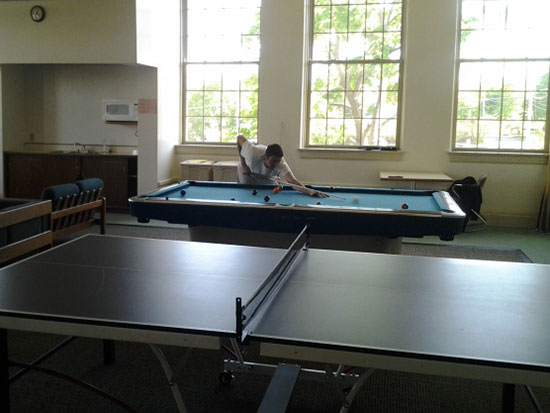 Student playing pool in Sheldon Hall main lounge. Kitchenette and ping-pong table too.