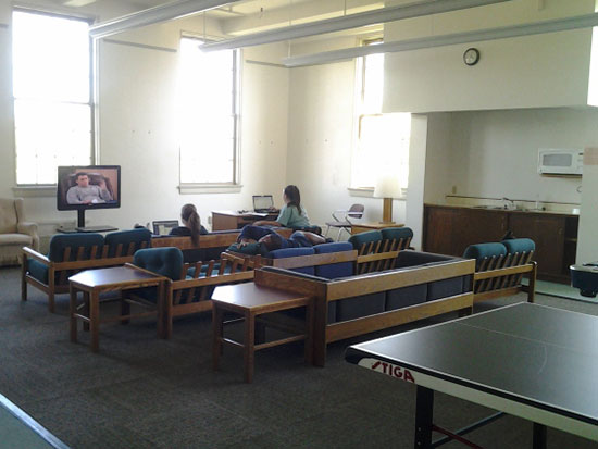 Students relax and watch television in the spacious and airy Sheldon Hall main lounge.