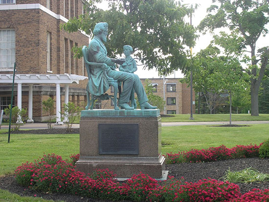 Statue of Edward Austin Sheldon, SUNY Oswego's founder, in front of Sheldon Hall with Moreland Hall in the background.