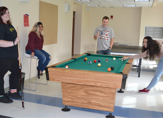 Friendly game of pool in the bright and airy Riggs Hall basement lounge.