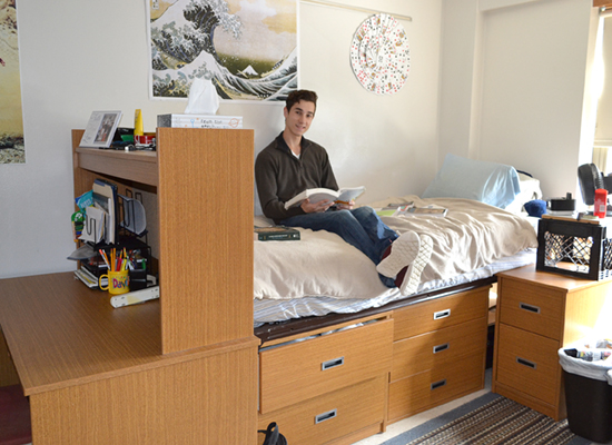 Hart Hall resident studies on his bed that is lofted high enough so that his dressers are slid underneath.