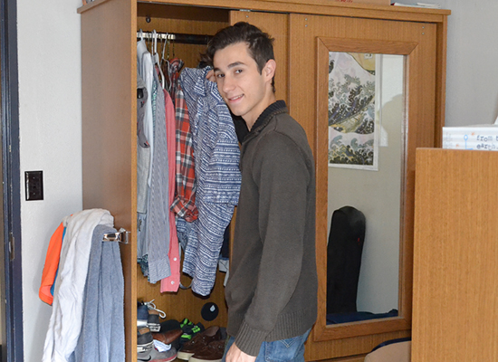 Hart Hall resident pauses for a photo while looking in his armoire for a shirt.