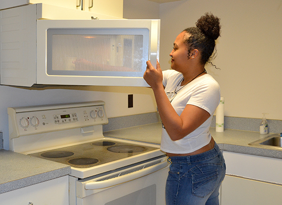 Hart Hall resident reaches for her tea in the microwave in the 3rd floor kitchenette.