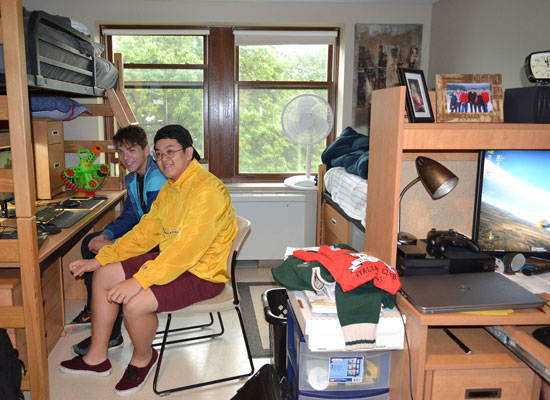 Male students in Johnson Hall work together in their room. The bed is bunked above a large worksurface with a hutch.