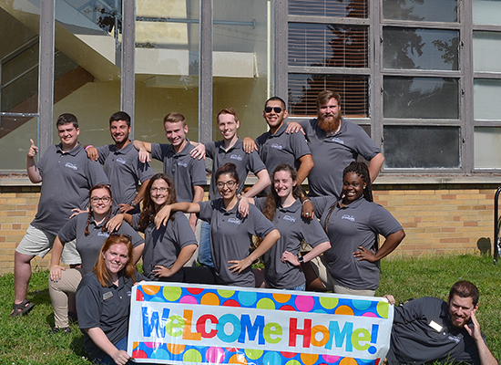 "Mackin Complex (Moreland and Lonis Halls) and Sheldon Hall staff pose for a group photo with a ""Welcome Home"" banner."