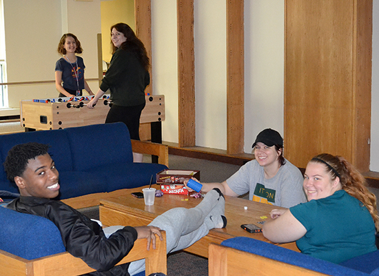 Cayuga Hall students enjoying the lounge area and playing foosball.