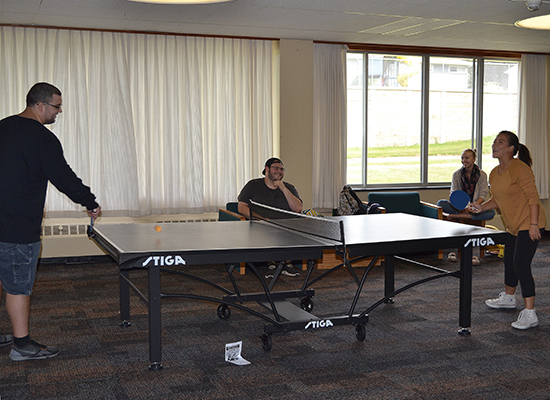 Students in the Funnelle Hall main lounge playing ping-pong.