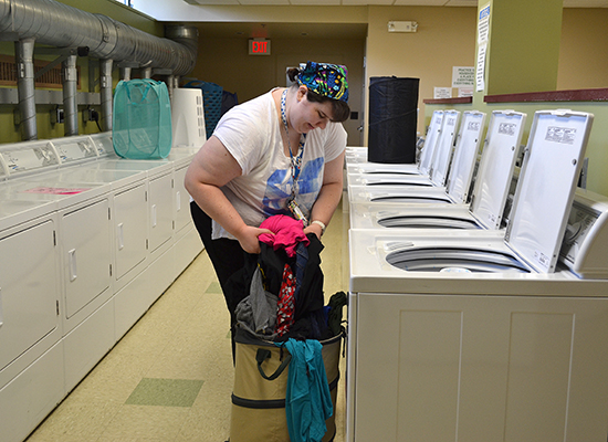 Student doing laundry in the Funnelle Hall clean and spacious laundry room.