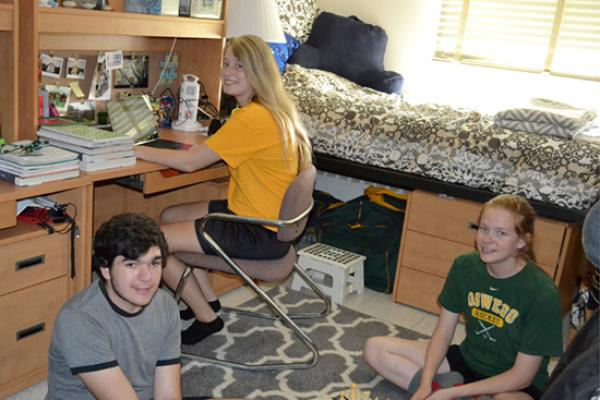 2 Oneida Hall residents do homework and play chess in their room with a friend.