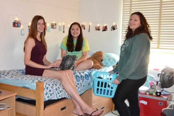 Students sit on their bed to study and chat with a friend on her way to the laundry room.