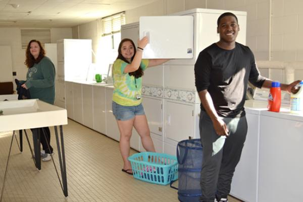 Male and female students share the clean and bright laundry room.