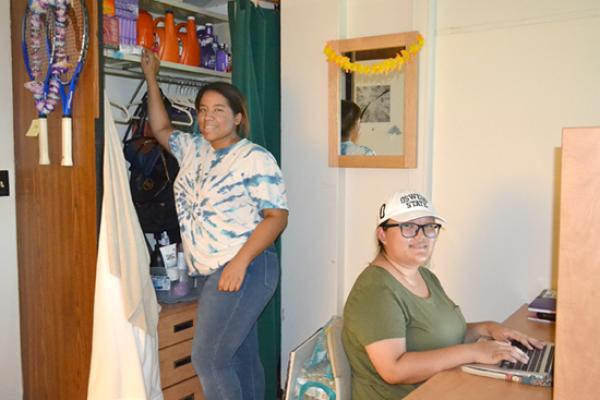 Seneca hall resident reaches up to grab something from her floor-to-ceiling closet while her roommate works at her desk.