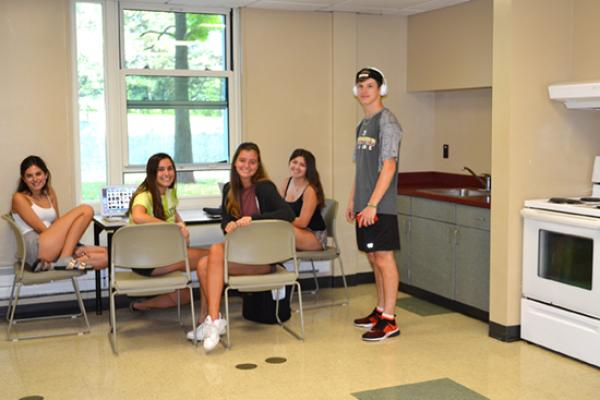 A group of residents study at a table in the kitchen area while doing their laundry next door in the Seneca Hall laundry room.