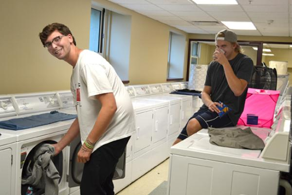 Seneca Hall residents in the bright, clean, large, and spacious laundry room.