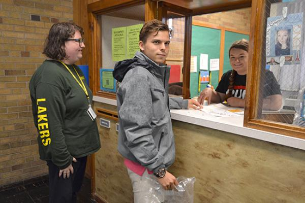 Students converse with the Desk Attendant at the Mackin Complex front desk.
