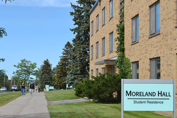 Moreland Hall (part of the Mackin Complex) sign on the side lawn of the building.