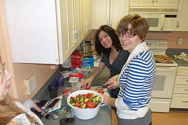 Mackin Complex main kitchen. 2 female students making a green salad.