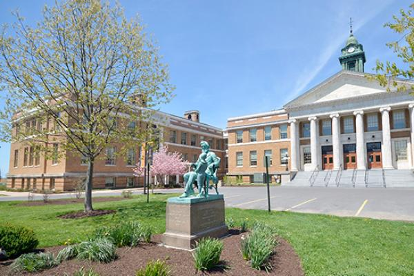 Sheldon Hall exterior in the spring with Edward Austin Sheldon statue.