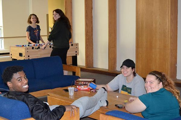 Cayuga Hall students enjoying the lounge area and playing foosball.