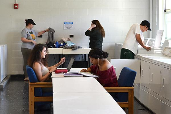 Cayuga Hall students doing their laundry while studying in our bright, sunny, and clean laundry room.