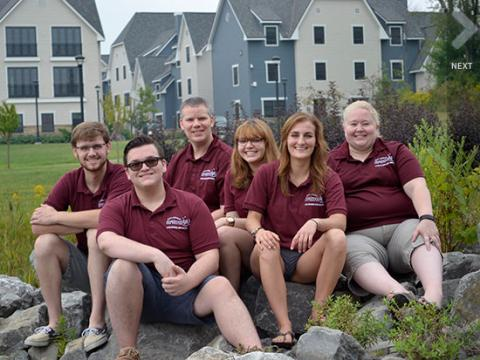 The Village staff sitting on rocks in front of the townhouses.