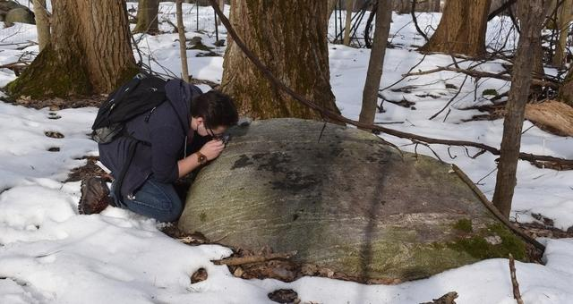 Student kneeling by large boulder in snow, examining the boulder with magnifying lens
