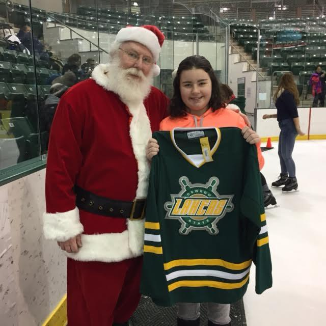One of the lucky winners of the hockey jersey raffle posing with our special guest SANTA!