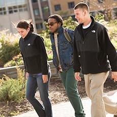 Three students walk across campus