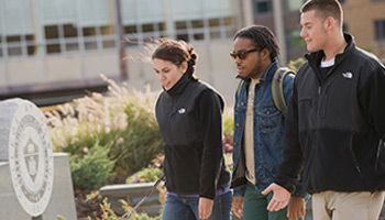 Three students walk across campus (deja vu!)