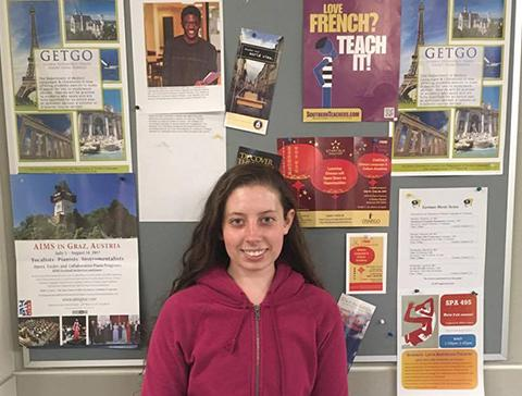 Serena Schaeber in front of bulletin board of opportunities