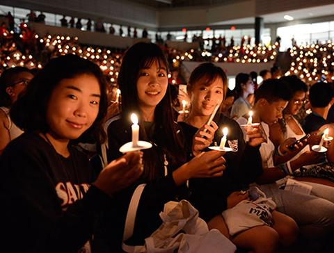 Students hold candles during Opening Torchlight