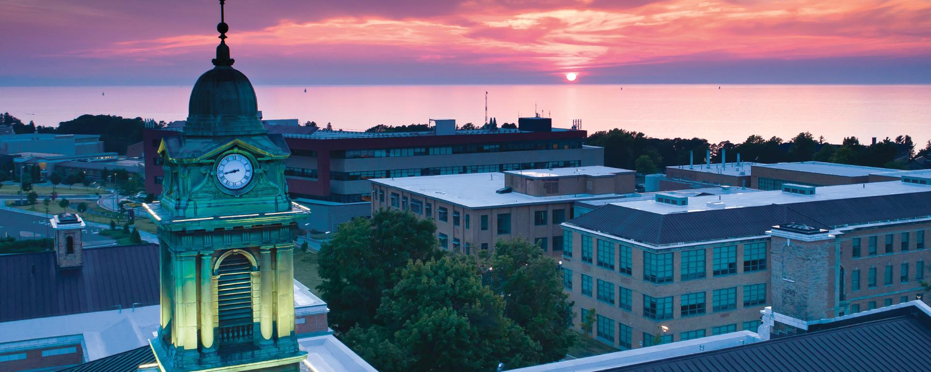 Aerial view of Sheldon Hall in front of a sunset