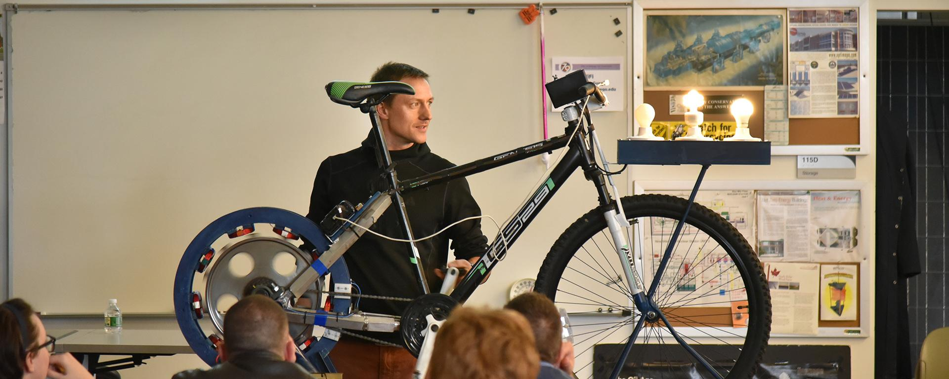 Presenter shows bicycle generating electricity