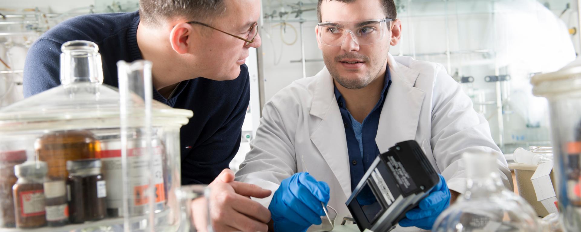 Professor Fehmi Damkaci and male student working in laboratory