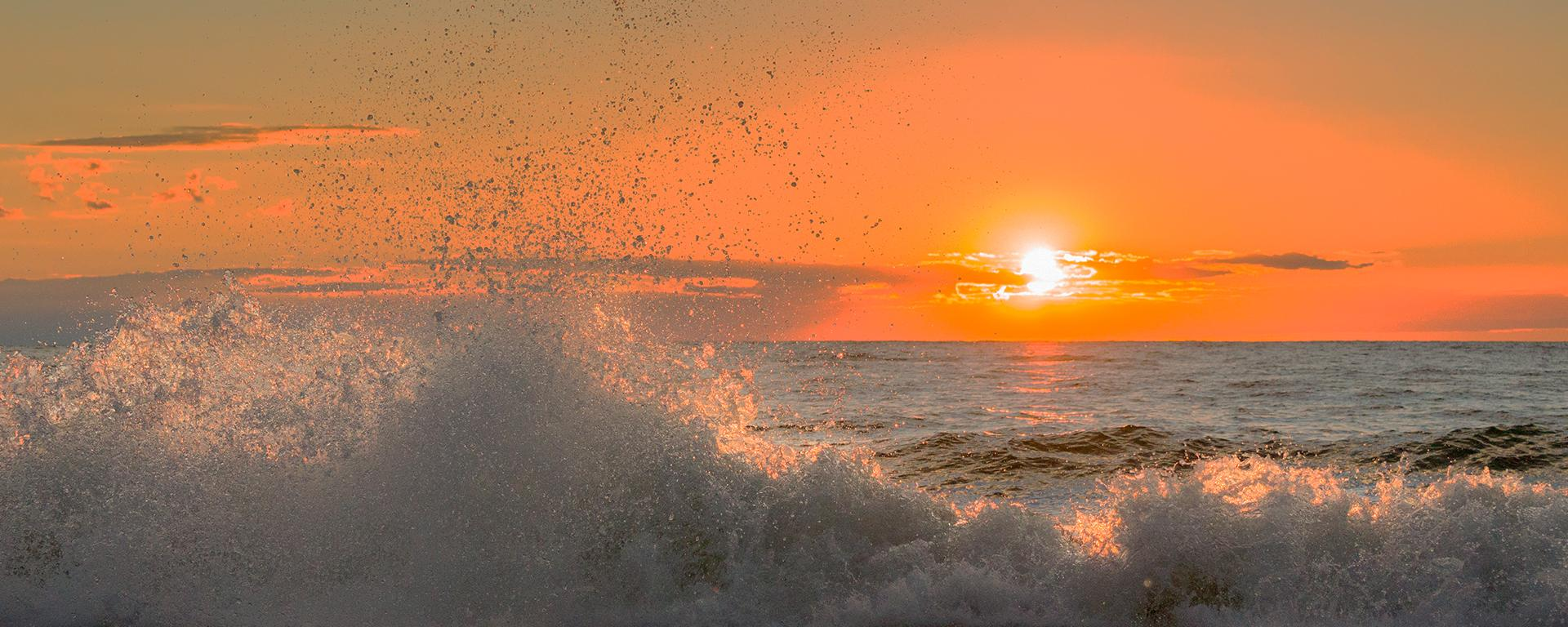 Waves on Lake Ontario in front of an orange sunset sky