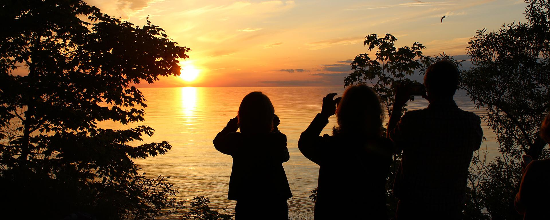 Alumni take photos of sunset over Lake Ontario