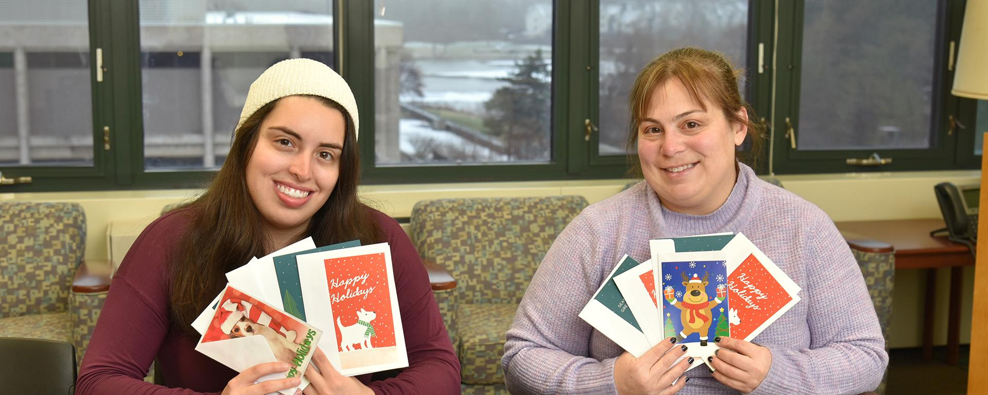 Faculty member Jaclyn Schildkraut is hosting card drive for kids who lost family members to mass shootings; student Sarah Gamarra helps her show off what they've received to date