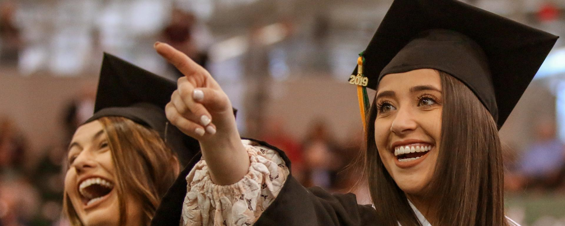 Student points to audience during Commencement